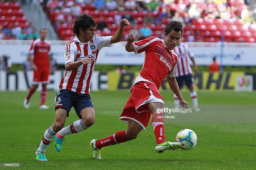 Irving Avalos (L) of Chivas struggles for the ball with Hector Acosta (R) of Toluca during the match between Chivas and Toluca as part of the Clausura 2013 Liga MX tournament at Omnilife Stadium on January 06, 2013 in Guadalajara, Mexico.