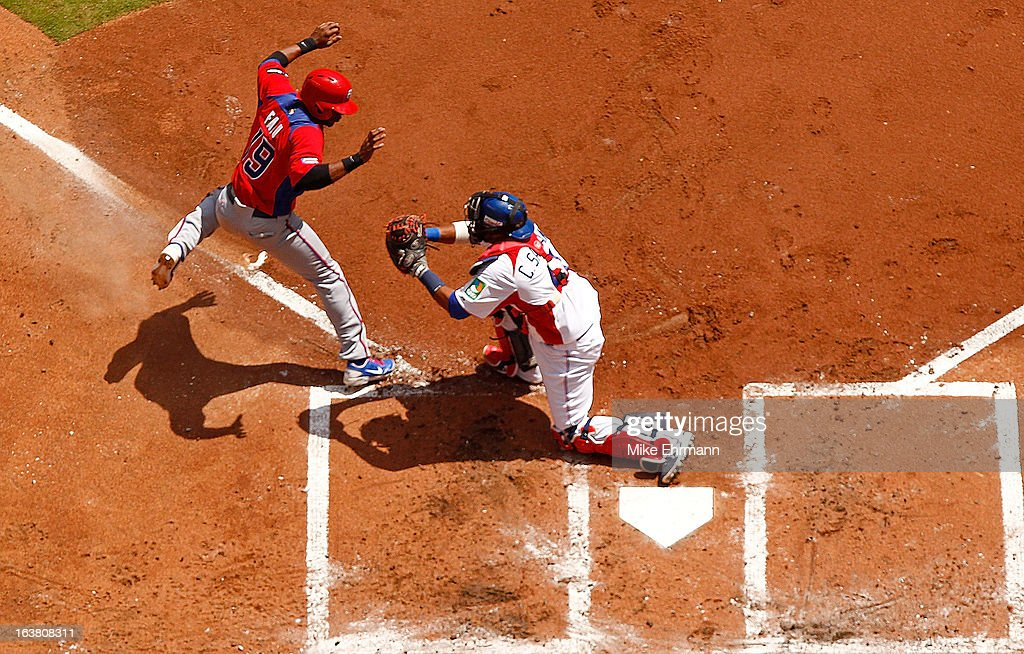 Irving Falu #19 of Puerto Rico is tagged out by Carlos Santana #41 of the Dominican Republic during a World Baseball Classic second round game at Marlins Park on March 16, 2013 in Miami, Florida.