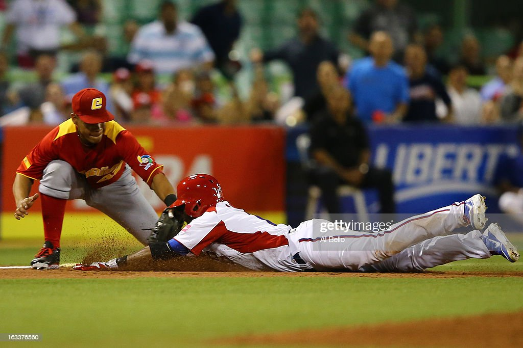 Irving Falu #19 of Puerto Rico is tagged out by Jesus Merchan #42 of Spain during the first round of the World Baseball Classic at Hiram Bithorn Stadium on March 8, 2013 in San Juan, Puerto Rico.