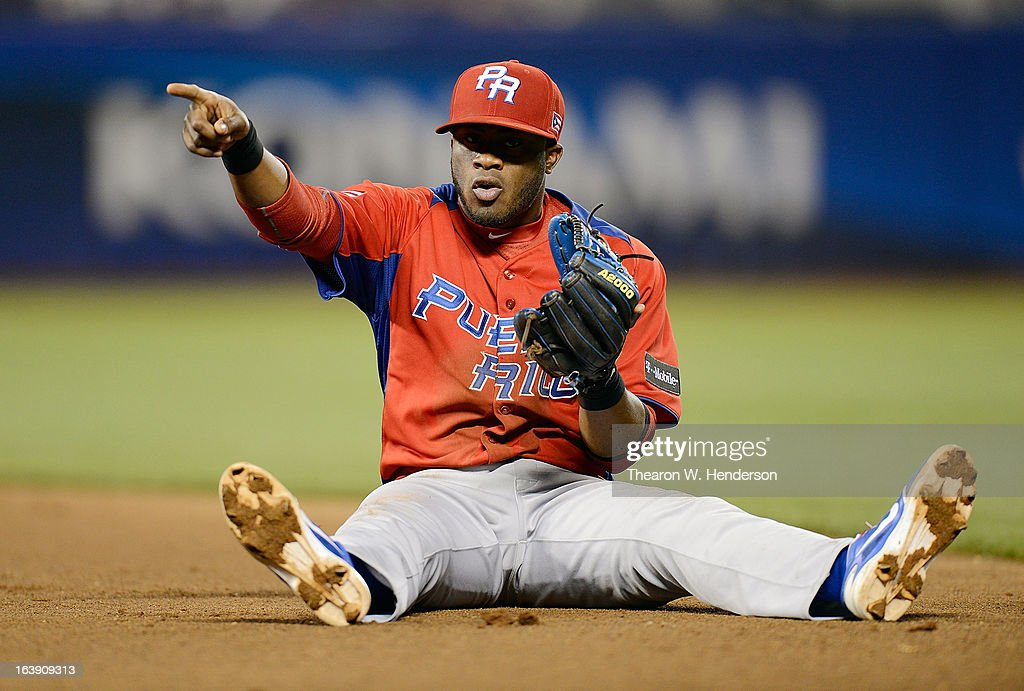 Irving Falu #19 of Team Puerto Rico points to his first baseman after throwing the Team Japan runner out sliding to the ground in the fifth inning during the World Baseball Classic Semifinals at AT&T Park on March 17, 2013 in San Francisco, California.