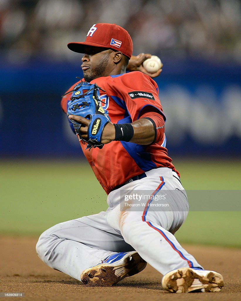 Irving Falu #19 of Team Puerto Rico throws the Team Japan runner out sliding to the ground in the fifth inning during the World Baseball Classic Semifinals at AT&T Park on March 17, 2013 in San Francisco, California.