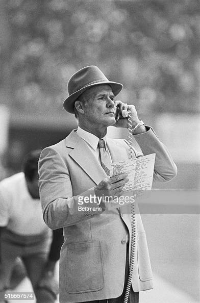 Cowboys coach Tom Landry looks over his selection of plays during 3rd quarter action against the Rams