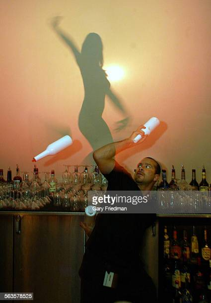 OLDAN is a bartender and juggles bottles during a routine behind the bar with go–go dancers in background at SHADOW BAR inside Caesar's Palace in Las...