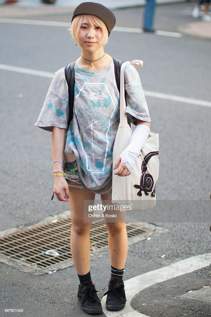 NAME is seen outside of Star Lounge wearing a Deadheartz tshirt crocheted black lowtop sneakers by Rowena an oversized camouflage backpack by Larkins...