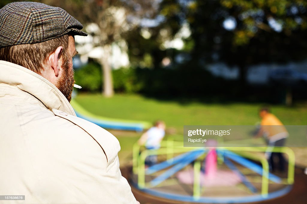 Is this a pedophile? Man watching children in park playground : Stock Photo