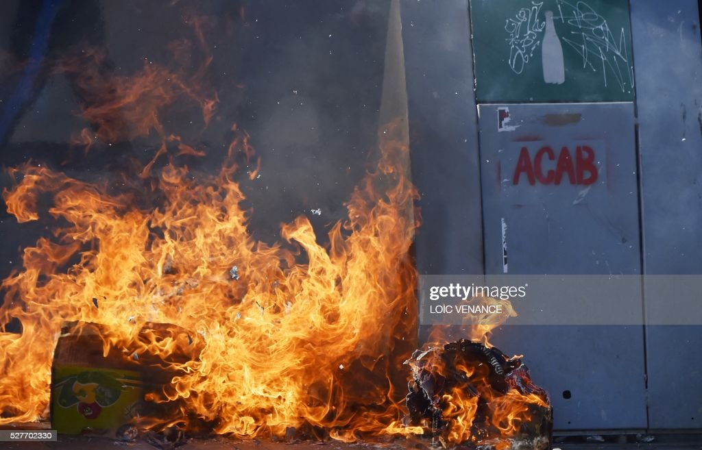 'ACAB' (All cops are bastards) is written on a burning trash container during a protest against the government's planned labour law reforms in Nantes, western France, on May 3, 2016. High school pupils and workers protested against deeply unpopular labour reforms that have divided the Socialist government and raised hackles in a country accustomed to iron-clad job security. / AFP / LOIC