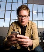 Isaac 'Biz' Stone cofounder and Creative Director of Twitter Inc tweets a message on his iPhone in their San Francisco California headquarters