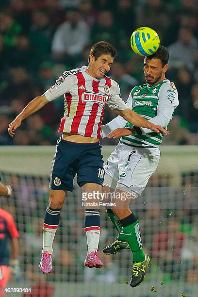 Isaac Brizuela of Chivas and Oswaldo Alanis of Santos jump for the ball during a match between Santos Laguna and Chivas as part of 5th round Clausura...
