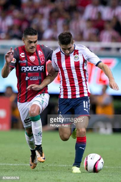 Isaac Brizuela of Chivas fights for the ball with Xavier Baez of Necaxa during the third round match between Chivas and Necaxa as part of the Torneo...