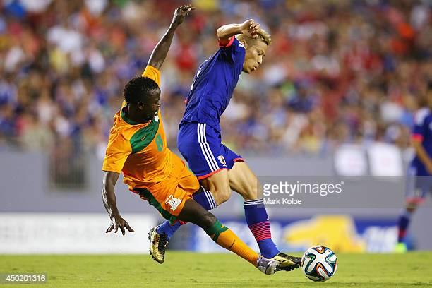 Isaac Chansa of Zambia tackles Keisuke Honda of Japan during the International Friendly Match between Japan and Zambia at Raymond James Stadium on...