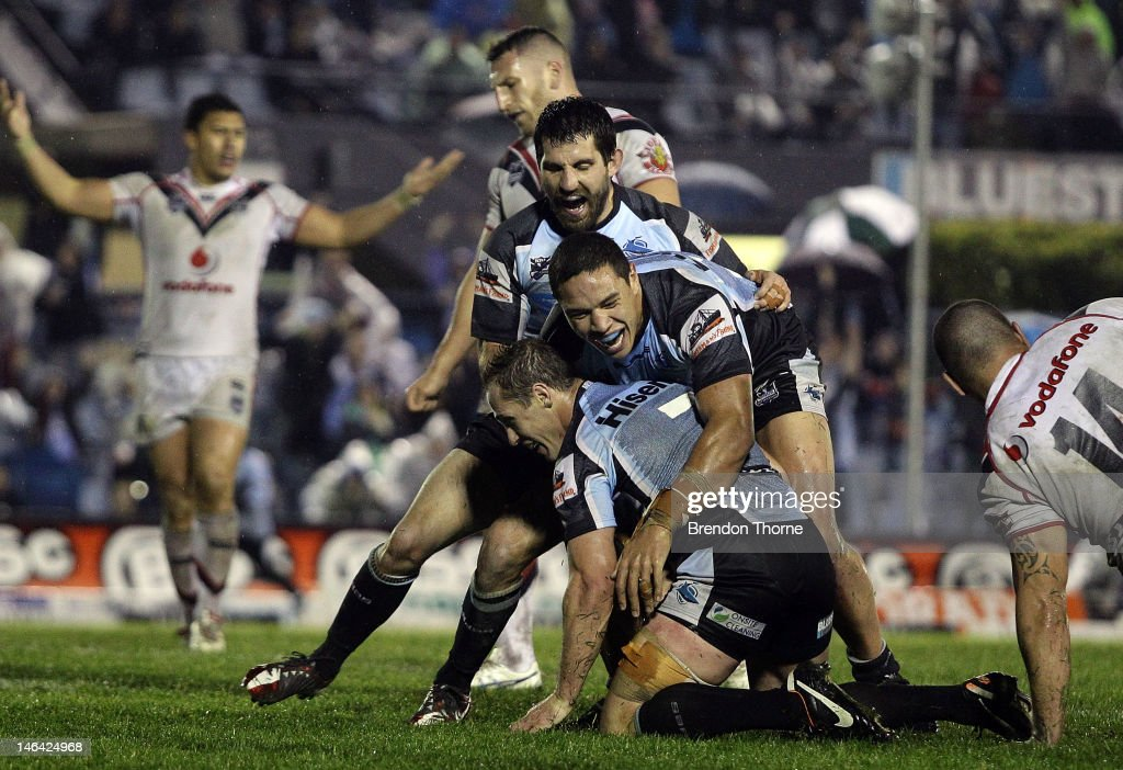 Isaac De Gois and Tyson Frizell of the Sharks celebrate with team mate Jeff Robson after he scored the winning try during the round 15 NRL match...