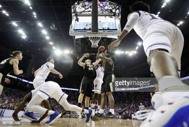 Isaac Haas of the Purdue Boilermakers and Dwight Coleby of the Kansas Jayhawks battle for a rebound in the first half during the 2017 NCAA Men's...