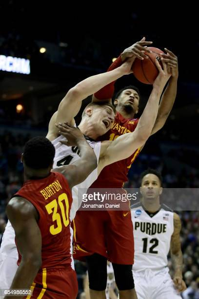 Isaac Haas of the Purdue Boilermakers battles for a rebound against Deonte Burton and Darrell Bowie of the Iowa State Cyclones in the first half...
