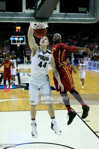 Isaac Haas of the Purdue Boilermakers dunks the ball while being guarded by Solomon Young of the Iowa State Cyclones in the first half during the...
