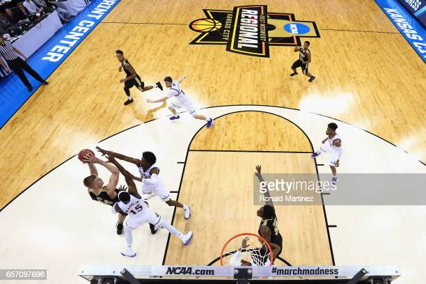 Isaac Haas of the Purdue Boilermakers handles the ball against Carlton Bragg Jr #15 and Josh Jackson of the Kansas Jayhawks during the 2017 NCAA...