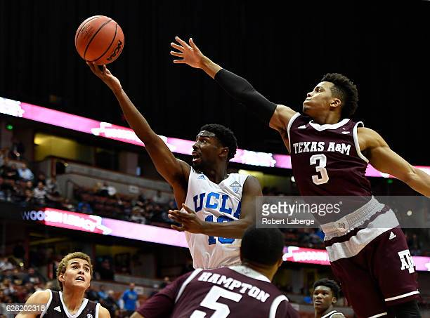 Isaac Hamilton of the UCLA Bruins attempts a layup as Admon Gilder of the Texas AM Aggies tries to block him during the championship game of the...