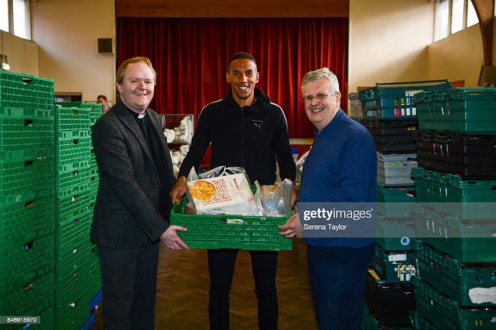 Isaac Hayden (C) of Newcastle United poses for photos with Reverend Dominic Coad (L) Vicar of Church of the Venerable Bede and Mike Nixon (R) Foodbank CEO during a visit to Newcastle West End Foodbank on September 14, 2017, in Newcastle upon Tyne, England.