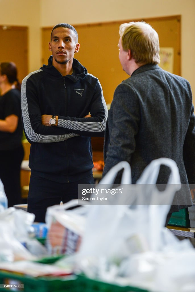 Isaac Hayden of Newcastle United talks with Reverend Dominic Coad (L) Vicar of Church of the Venerable Bede during a visit to Newcastle West End Foodbank on September 14, 2017, in Newcastle upon Tyne, England.