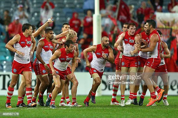 Isaac Heeney of the Swans celebrates kicking a goal with team mates during the Round One AFL match between the Sydney Swans and the Essendon Bombers...