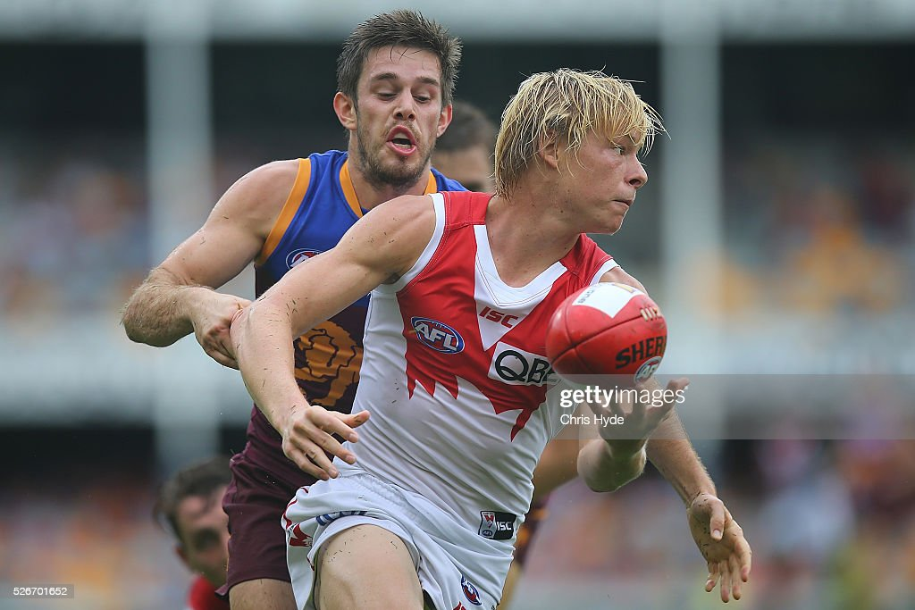 Isaac Heeney of the Swans handballs during the round six AFL match between the Brisbane Lions and the Sydney Swans at The Gabba on May 1, 2016 in Brisbane, Australia.