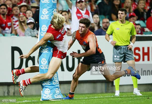 Isaac Heeney of the Swans hits the post after kicking a goal as Tomas Bugg of the Giants looks on during the round three AFL match between the Sydney...