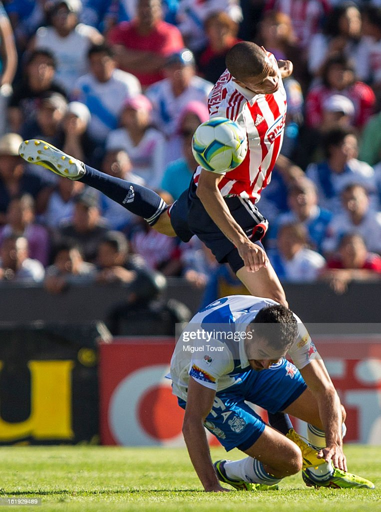 Isaac Romo (L) of Puebla fights for the ball with Jorge Enriquez (R) of Chivas during a match between Puebla and Chivas as part of the Clausura 2013 at Cuauhtemoc Stadium on February 17, 2013 in Puebla, Mexico.