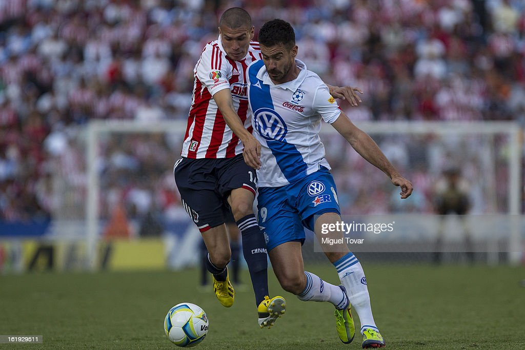 Isaac Romo (R) of Puebla fights for the ball with Jorge Enriquez (L) of Chivas during a match between Puebla and Chivas as part of the Clausura 2013 at Cuauhtemoc Stadium on February 17, 2013 in Puebla, Mexico.