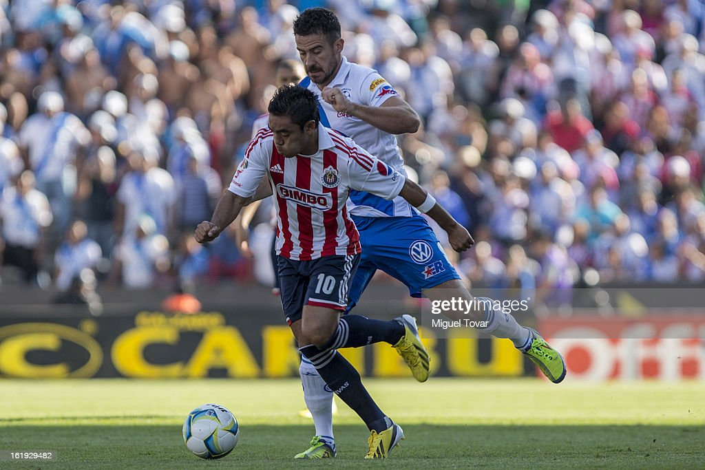 Isaac Romo (R) of Puebla fights for the ball with Marco Fabian (L) of Chivas during a match between Puebla and Chivas as part of the Clausura 2013 at Cuauhtemoc Stadium on February 17, 2013 in Puebla, Mexico.