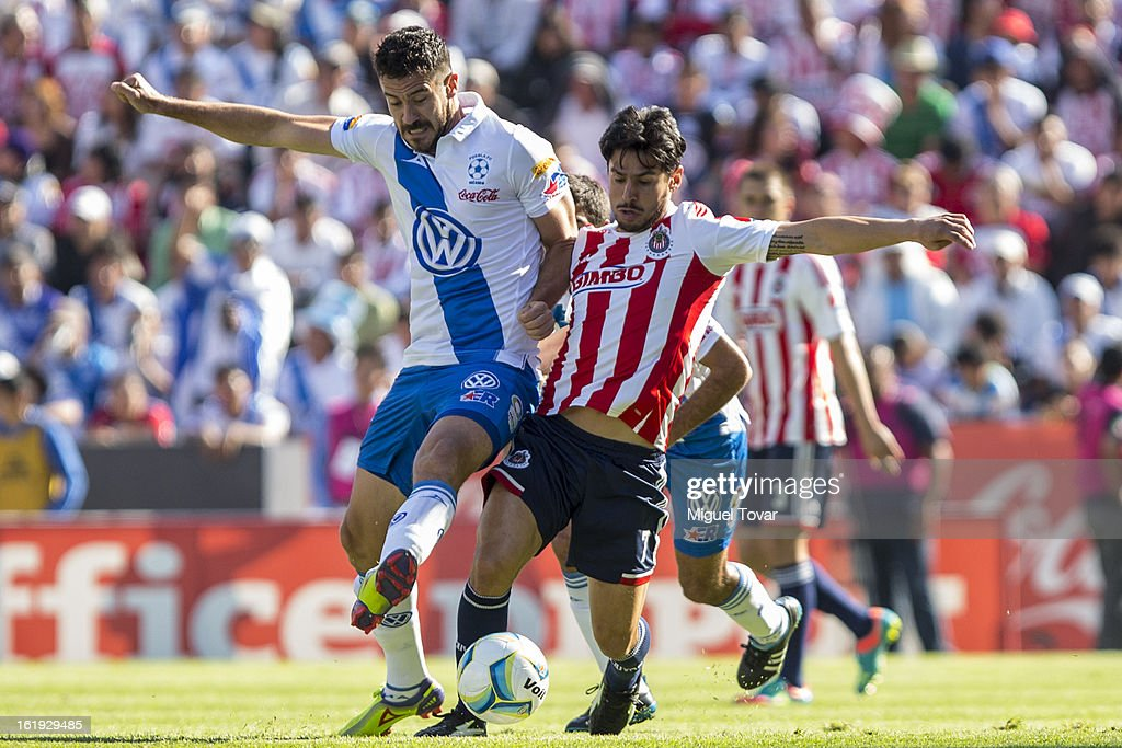 Isaac Romo (L) of Puebla fights for the ball with Rafael Marquez (R) of Chivas during a match between Puebla and Chivas as part of the Clausura 2013 at Cuauhtemoc Stadium on February 17, 2013 in Puebla, Mexico.