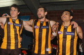 Isaac Smith Luke Hodge and Cyril Rioli of the Hawks celebrate in the rooms after the round 13 AFL match between the Hawthorn Hawks and the Gold Coast...