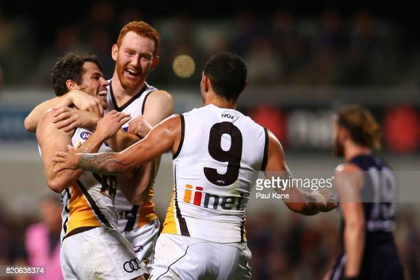 Isaac Smith of the Hawks celebrates a goal with Conor Glass and Shaun Burgoyne during the round 18 AFL match between the Fremantle Dockers and the...
