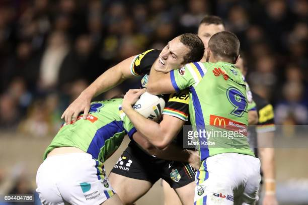 Isaah Yeo of the Panthers is tackled by Joseph Leilua and Josh Hodgson of the Raiders during the round 14 NRL match between the Penrith Panthers and...