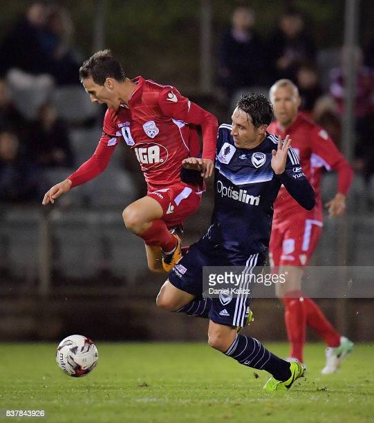 Isaas Sanchez of United and Mark Milligan of the Victory compete for the ball during the round of 16 FFA Cup match between Adelaide United and...