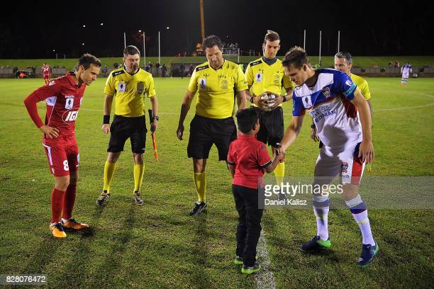Isaas Sanchez of United and Nigel Boogaard of Newcastle attend the coin toss prior to the round of 32 FFA Cup match between Adelaide United and the...