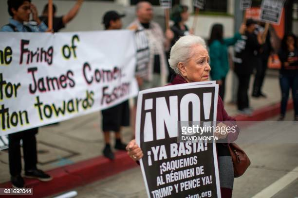 Isabel Cardenas holds a sign on May 10 2017 in Los Angeles California as protestors denounce the firing of FBI Director James Comey by US President...