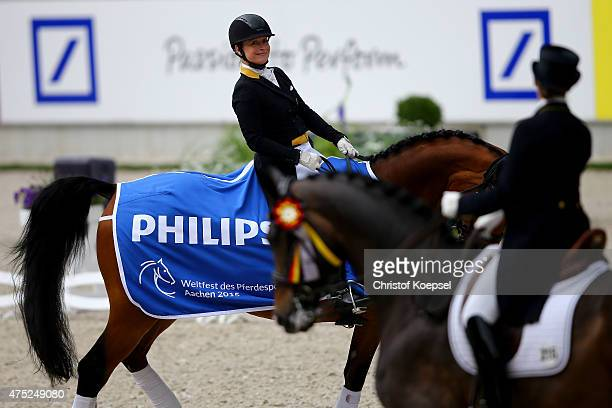Isabell Werth of Germany rides on Don Johnson FRH and celebrates her victory during gthe ceremony of the dressage GrandPrix CDI competition during...