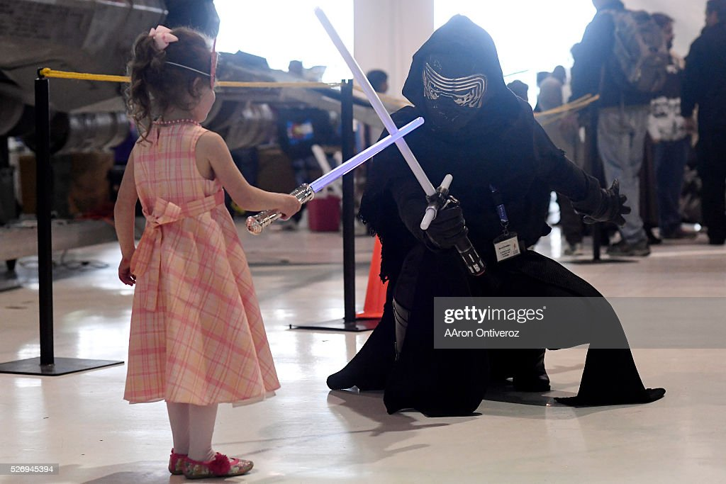 Isabelle Aisch touches light sabers with an X-Wing ground support unit worker during a Star Wars themed day at Wings Over the Rockies on Sunday, May 1, 2016.