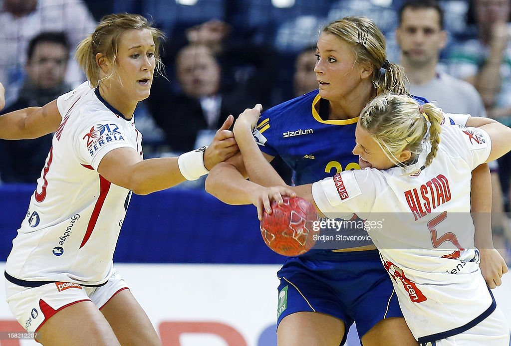 Isabelle Gullden (C) is challenged by Ida Alstad (R) and Marit Malm Frafjord (R) of Norway during the Women's European Handball Championship 2012 Group I main round match between Norway and Sweden at Arena Hall on December 11, 2012 in Belgrade, Serbia.