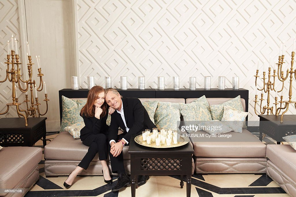 Isabelle Huppert wearing a Dior Smoking poses with Viggo Mortensen in the lounge of the Mandarin Oriental Hotel during the 14th Film Festival of...