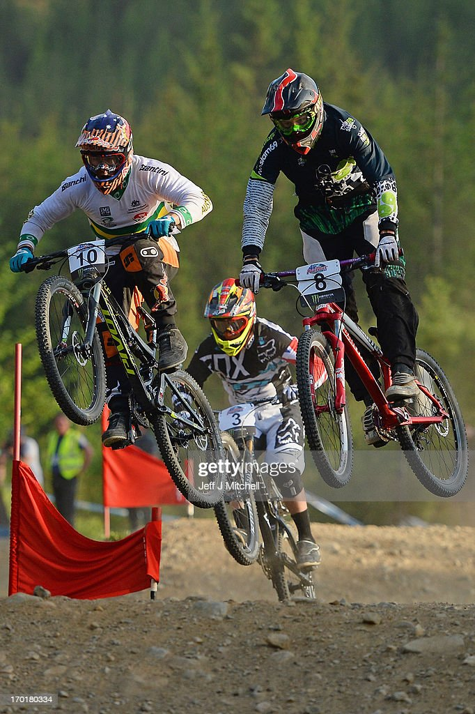 Isacc Munday, Joseph Venjoda and Scott Beaunont competes in the men's four cross pro tour qualification at the UCI Mountain Bike World Cup on June 8, 2013 in Fort William, Scotland.