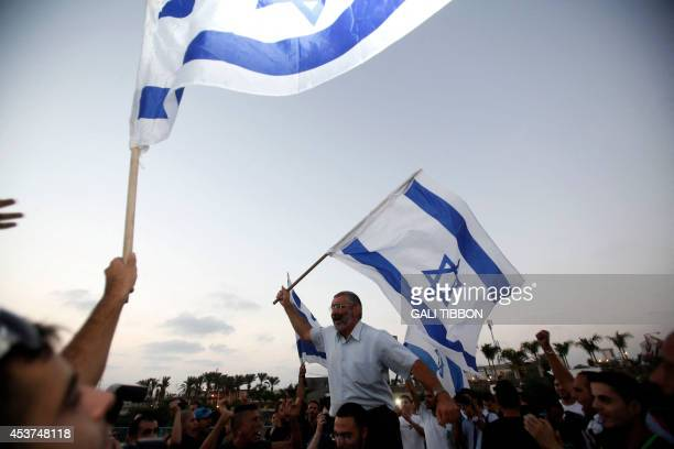 Isaeli supporters of the rightwing Organization for Prevention of Assimilation in the Holy Land wave the national flag as they protest outside the...