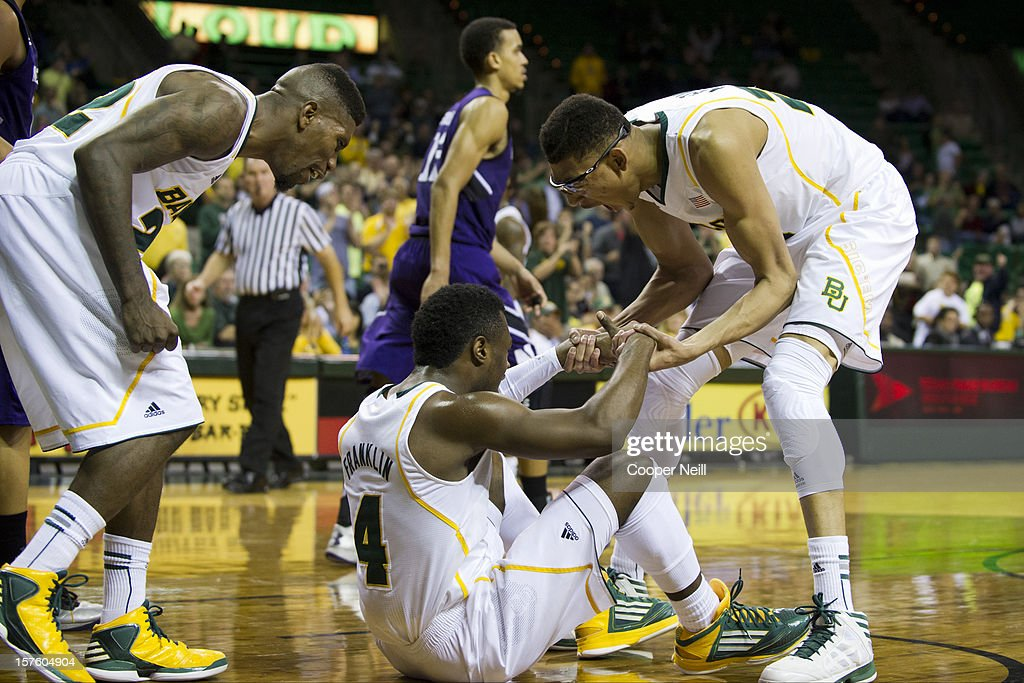 <a gi-track='captionPersonalityLinkClicked' href=/galleries/search?phrase=Isaiah+Austin&family=editorial&specificpeople=9082709 ng-click='$event.stopPropagation()'>Isaiah Austin</a> #21 and A.J. Walton #22 of the Baylor University Bears help up teammate Gary Franklin #4 after he took a charge against the Northwestern University Wildcats on December 4, 2012 at the Ferrell Center in Waco, Texas.