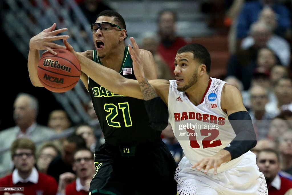 Isaiah Austin #21 of the Baylor Bears and Traevon Jackson #12 of the Wisconsin Badgers go after the ball in the first half during the regional semifinal of the 2014 NCAA Men's Basketball Tournament at the Honda Center on March 27, 2014 in Anaheim, California.