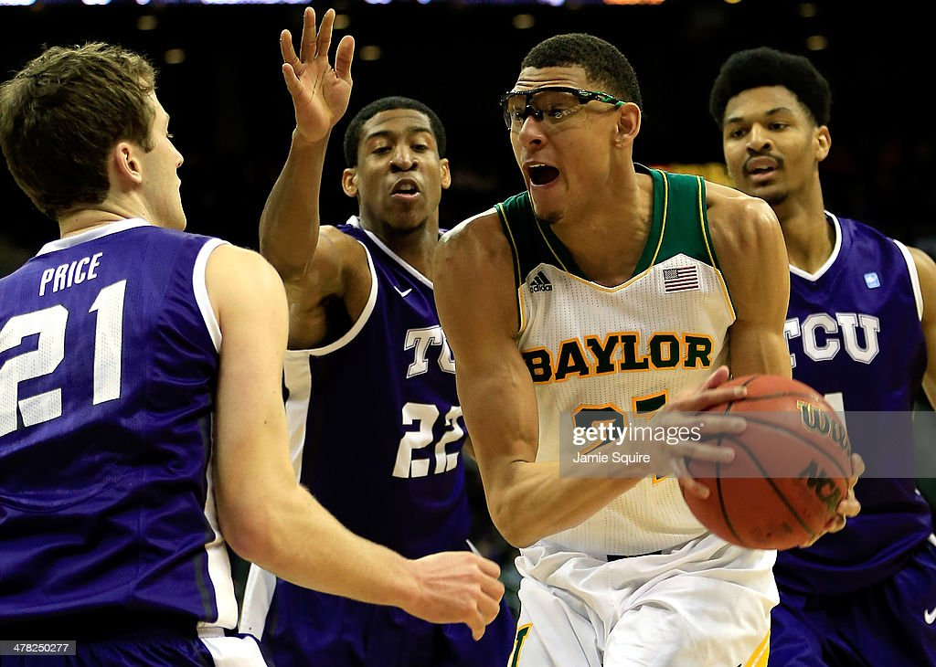Isaiah Austin of the Baylor Bears controls the ball as Hudson Price and Jarvis Ray of the TCU Horned Frogs defend during the Big 12 Basketball...