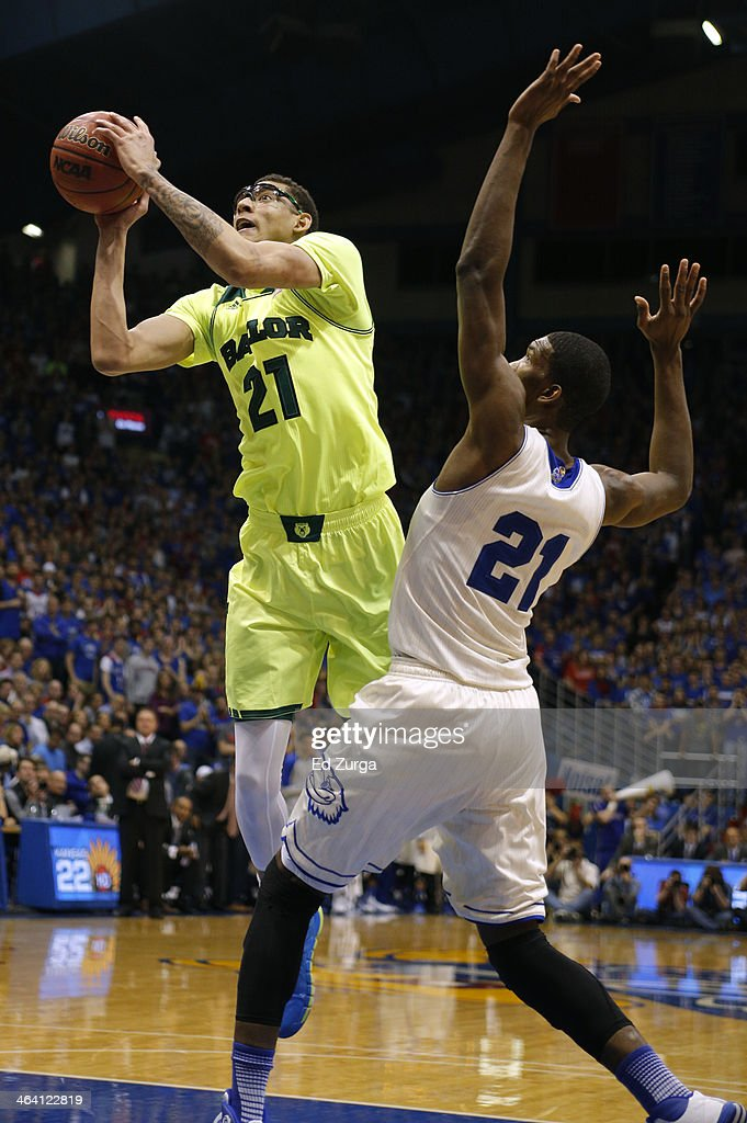 Isaiah Austin of the Baylor Bears shoots around Joel Embiid of the Kansas Jayhawks in the second half at Allen Fieldhouse on January 20 2014 in...