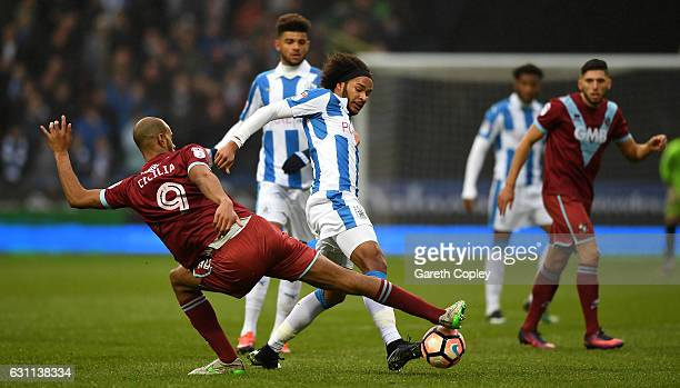 Isaiah Brown of Huddersfield is tackled by Rigino Cicilia of Port Vale during The Emirates FA Cup Third Round match between Huddersfield Town and...