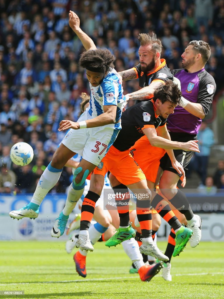 Isaiah Brown of Huddersfield Town, Steven Fletcher of Sheffield Wednesday, Keiren Westwood of Sheffield Wednesday and Kieran Lee of Sheffield Wednesday all battle to win a header during the Sky Bet Championship Play Off Semi Final 1st leg match between Huddersfield Town and Sheffield Wednesday at Galpharm Stadium on May 14, 2017 in Huddersfield, England.
