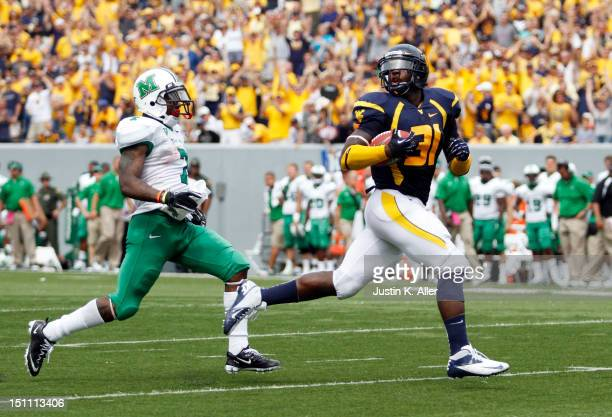 Isaiah Bruce of the West Virginia Mountaineers returns a fumble for a touchdown in the third quarter against the Marshall Thundering Herd during the...