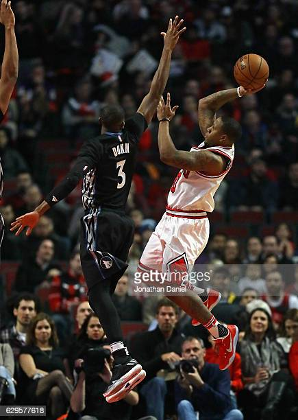 Isaiah Canaan of the Chicago Bulls goes up for a shot against Kris Dunn of the Minnesota Timberwolves at the United Center on December 13 2016 in...