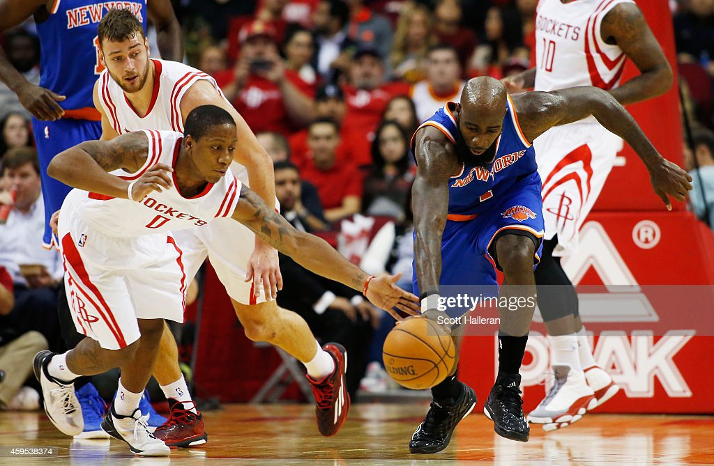 Isaiah Canaan #0 of the Houston Rockets and Quincy Acy #4 of the New York Knicks battle for a loose ball during their game at the Toyota Center on November 24, 2014 in Houston, Texas.